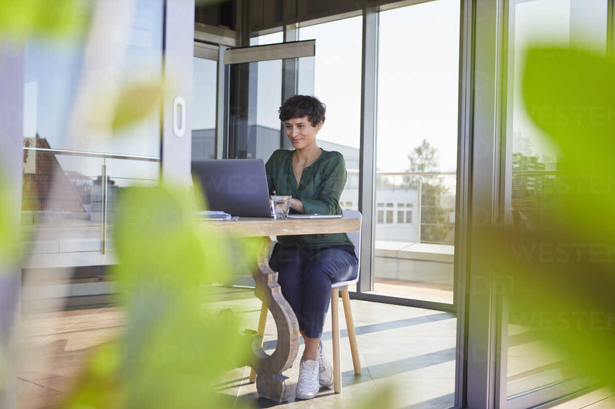 Smiling businesswoman sitting at table using laptop - RBF06863 - Rainer Berg/Westend61