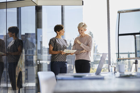 Two smiling businesswomen discussing document at the window in office - RBF06878