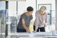 Two smiling businesswomen discussing plan on desk in office - RBF06881