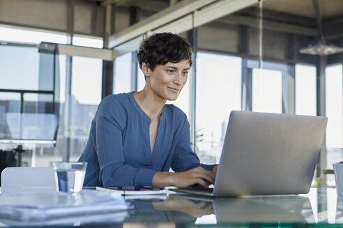 Businesswoman sitting at desk in office using laptop - RBF06884