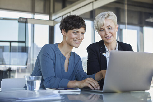 Two smiling businesswomen sharing laptop at desk in office - RBF06887