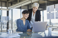Two smiling businesswomen sharing laptop at desk in office - RBF06890