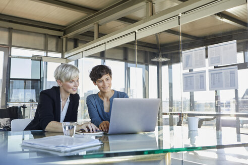 Two smiling businesswomen sharing laptop at desk in office - RBF06893