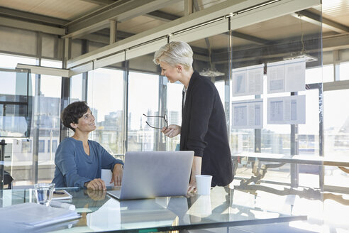 Two smiling businesswomen discussing at desk in office - RBF06896
