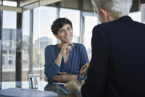 Two businesswomen talking at desk in office - RBF06899