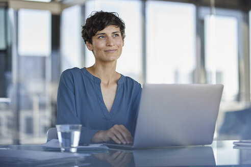 Smiling businesswoman sitting at desk in office with laptop - RBF06905
