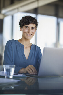 Portrait of confident businesswoman sitting at desk in office with laptop - RBF06908