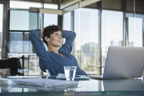 Smiling businesswoman sitting at desk in office with laptop having a break - RBF06911