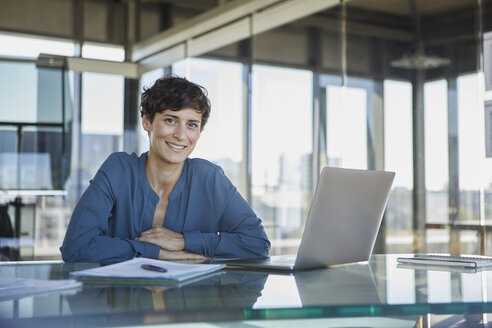 Portrait of confident businesswoman sitting at desk in office with laptop - RBF06914