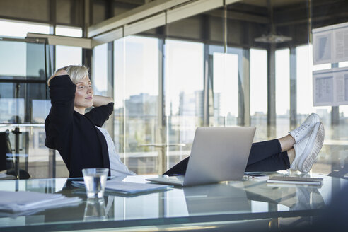 Businesswoman sitting at desk in office with closed eyes - RBF06917