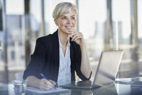 Portrait of confident businesswoman sitting at desk in office with laptop - RBF06920