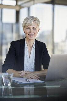 Portrait of smiling businesswoman sitting at desk in office with laptop - RBF06923