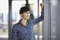Smiling businesswoman in office looking out of window - RBF06929
