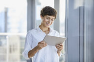Smiling businesswoman using tablet at the window in office - RBF06932