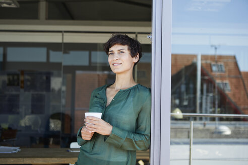 Smiling woman standing at the window having a coffee break - RBF06941