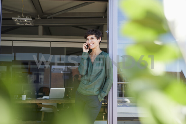 Smiling woman standing at the window talking on cell phone - RBF06944 - Rainer Berg/Westend61