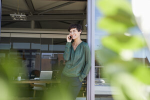 Smiling woman standing at the window talking on cell phone - RBF06944