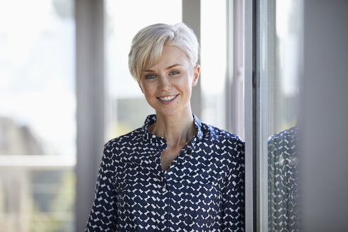 Portrait of smiling businesswoman in office - RBF06947