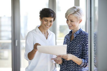Two smiling businesswomen looking at document at the window in office - RBF06950