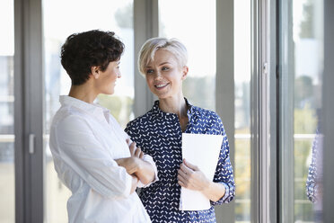 Two smiling businesswomen talking at the window in office - RBF06953
