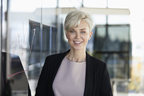 Portrait of smiling businesswoman next to chart on glass pane in office - RBF06959