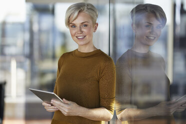 Portrait of smiling businesswoman with tablet at the window - RBF06965