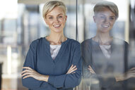 Portrait of smiling woman leaning against window - RBF06971