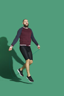 Portrait of bearded man skipping rope in front of green backgrpund - VGF00147