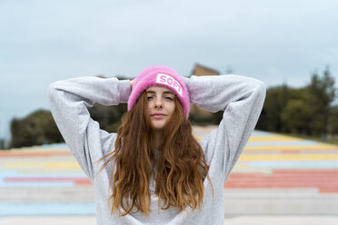 Portrait of smiling redheaded woman wearing pink cap with the word 'soft' - AFVF02179