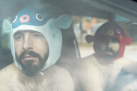 Portrait of gay couple in a car wearing animal hats - AFVF02182