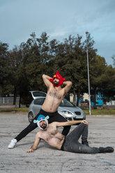 Gay couple wearing animal hats posing at car park - AFVF02185