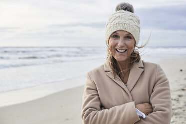 Headshot of an elegant senior woman looking at camera with folded arms at the beach in winter. Menorca, Spain. - IGGF00705