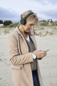 Spain, Menorca, senior woman using smartphone and wireless headphones  on the beach in winter - IGGF00708