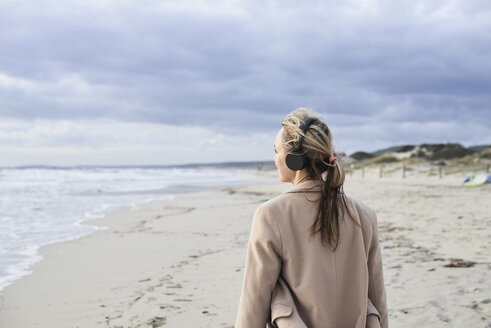 Spain, Menorca, back view of senior woman listening music with wireless headphones on the beach in winter - IGGF00711