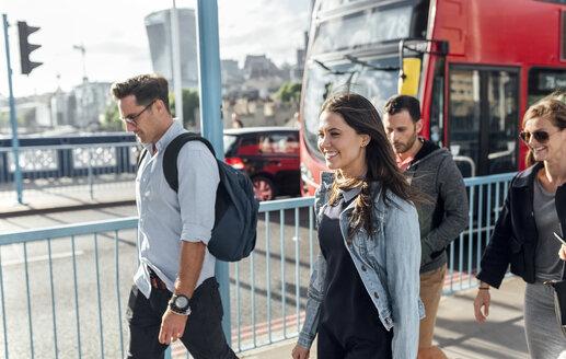 UK, London, happy friends walking on the Tower Bridge - MGOF03893