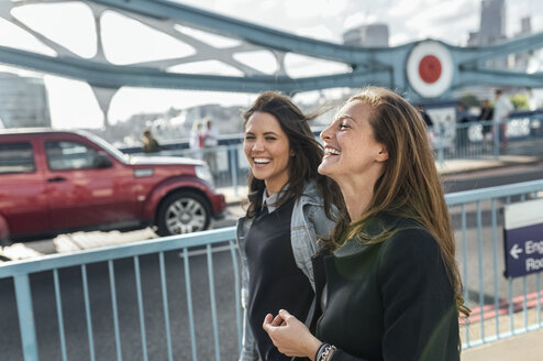 UK, London, two happy women walking on the Tower Bridge - MGOF03896