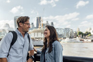 UK, London, smiling couple with skyline in the background - MGOF03899