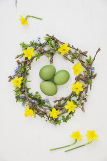 Self-made Easter wreath and green dyed eggs on white ground - GWF05748
