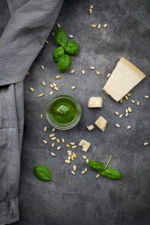 Glass of homemade pesto Genovese, pine nuts, basil leaves and parmesan on grey ground - LVF07616