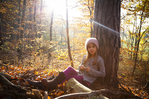 Young girl sitting on tree in autumn - LVF07632