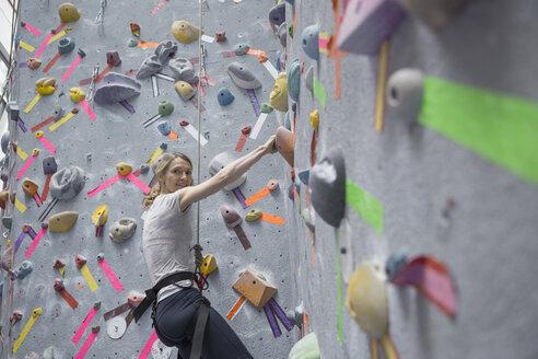 Portrait of woman climbing indoor wall - HEROF03574