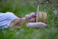 Portrait of laughing teenage girl wearing straw hat lying on a meadow in summer - LBF02315
