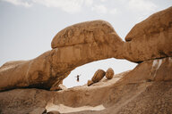 Namibia, Spitzkoppe, woman jumping at rock formation - LHPF00349