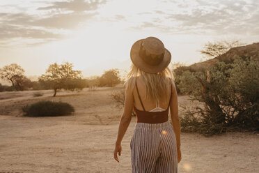 Namibia, Spitzkoppe, rear view of woman with hat at sunset - LHPF00361