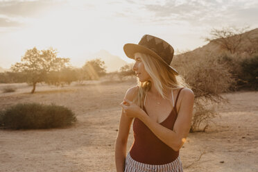 Namibia, Spitzkoppe, woman with hat at sunset - LHPF00364
