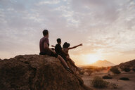 Namibia, Spitzkoppe, friends sitting on a rock watching the sunset - LHPF00370