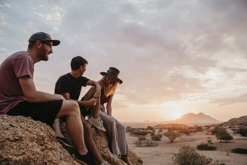 Namibia, Spitzkoppe, friends sitting on a rock at sunset - LHPF00376