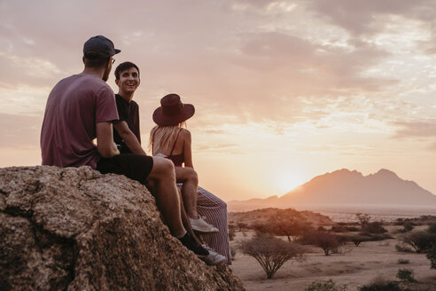 Namibia, Spitzkoppe, friends sitting on a rock at sunset - LHPF00379