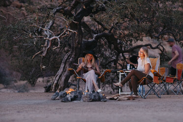 Namibia, friends sitting at campfire playing guitar - LHPF00382
