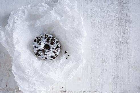 Doughnut with white icing and dark chocolate chips on white tissue paper - OJF00318